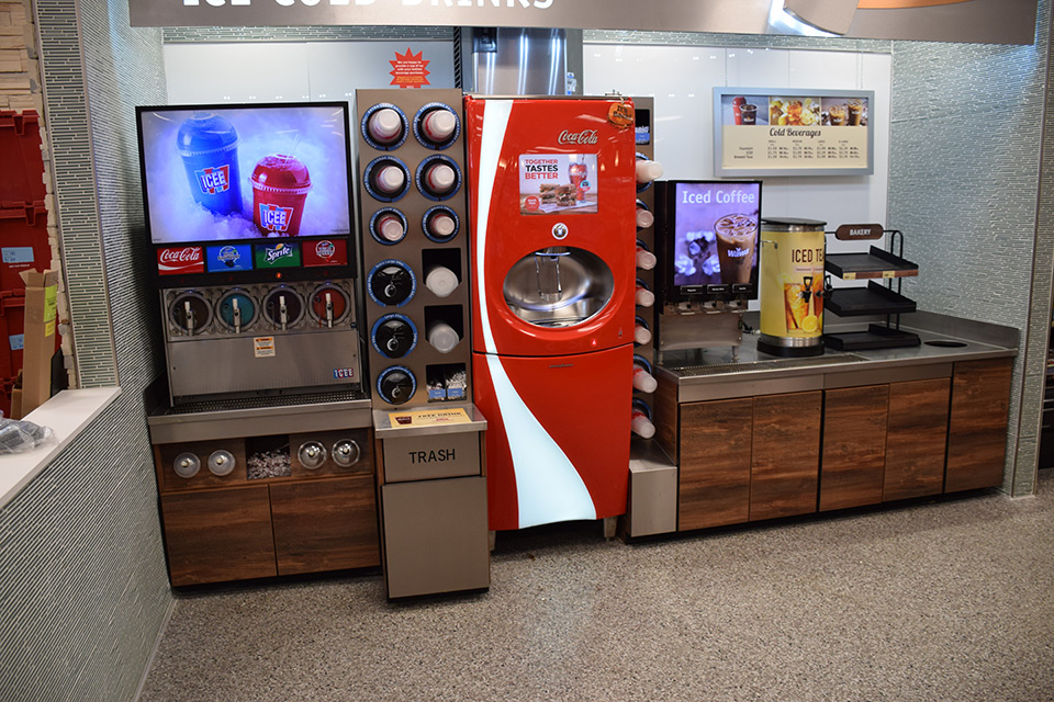 Wawa coffee fixture with cups, lids, cream, sugars, and straws