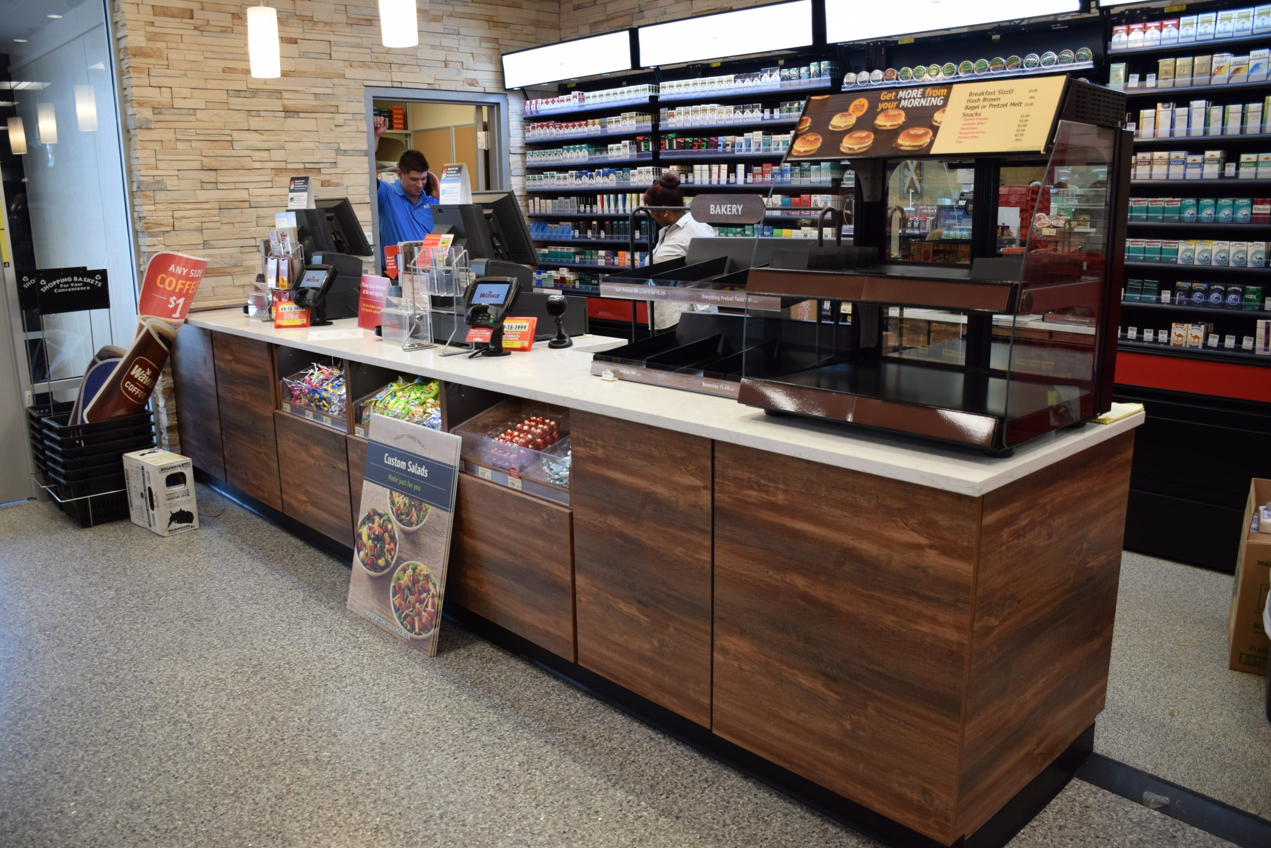 Wawa cigarette checkout area with point-of-sale candy and a breakfast sandwich display case
