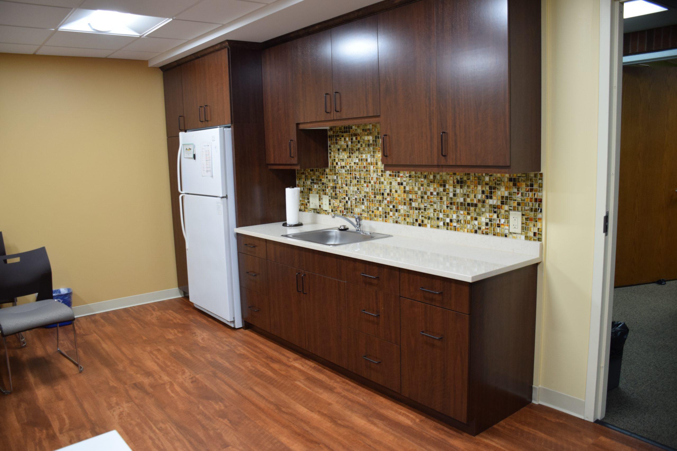 Pediatric kitchen area including custom cabinetry, refrigerator, sink, and colorful tile backsplash